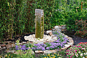 Granitsäule als Wasserspiel, eingefaßt mit Natursteinen, dahinter Phyllostachys nigra (Schwarzer Bambus), Bogen aus Ageratum (Leberbalsam)