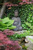 Nische mit Buddha-Figur auf Trockenmauer , Wand bewachsen mit Hedera (Efeu), Hosta (Funkie)