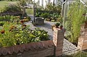 Kleiner Bauerngarten mit Mauer, Brunnen in der Mitte, gepflasterte Wege,
