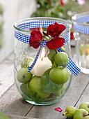 Einmachglas als Windlicht mit Kerze auf grünen Äpfeln (Malus)