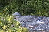 Interessant gepflasterte kleine Terrasse zwischen Beeten