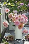 Strauß aus rosa Dahlia (Dahlien) in weißer Kanne, Kranz aus Hydrangea