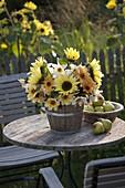 Strauß aus Helianthus (Sonnenblumen) und Dahlia (Dahlien) in Holzkübel