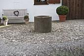 Offener Vorgarten mit Brunnen auf Steckkieselpflaster