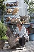 Junge Frau reinigt Korb mit Bürste, Körbe and Wand gehängt und auf Tisch