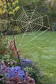 Selbstgemachtes Spinnennetz aus gebogenem Zweig und Rupfen im Herbstbeet