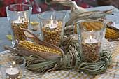 Bienchengläser mit Maiskörnern und Teelichtern als Windlichter