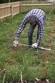 Gartenplanung : Mann mißt Wegbreite und zeichnet mit Farbpulver an