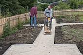 Männer legen Weg aus Schotter an, mit Rüttelplatte verfestigen