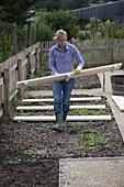 Frau legt Holzroste als Wege im gleichmäßigen Abstand in die Beete