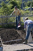 Frau legt Holzrost als Weg in fertig vorbereitetes Beet, Mann mit Schaufel