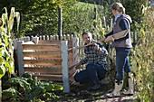 Mann und Frau bauen zusammen Kompost-Behälter auf