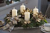 Weiß-goldener Adventskranz mit weißen Kerzen