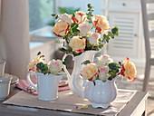 Rosa 'Double Delight' und 'Fedora' (Rosen) mit Eukalyptus in Porzellankannen
