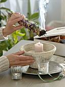 Räucherkolben aus getrockneten Kräutern über Kerze anzünden