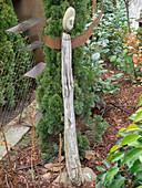 Figur aus Holz mit Armen aus Eisen und Kopf aus Kieselstein neben Thuja