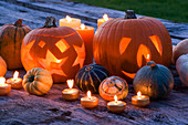 Halloween: STILL LIFE On WOODEN TABLE at NIGHT with CANDLES, PUMPKINS, SQUASHES AND GOURDS