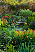 WOLLERTON Old HALL, SHROPSHIRE. A PLACE TO SIT. Metal SEAT AND VIEW ACROSS LANHYDROCK Garden with CROCOSMIA 'CONSTANCE' AND ERYSIMUM 'Apricot DELIGHT' IN FOREGROUND.