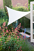 PAULA PRYKES HOUSE, Suffolk: COURTYARD Garden with Canvas SAIL / CANOPT OVER SEATING AREA with CENTRANTHUS RUBER