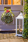 BRUERN COTTAGES, OXFORDSHIRE: CHRISTMAS - DECORATIVE HOLLY WREATH with Red BAUBLES AND RIBBON On Front DOOR with White LANTERN at NIGHT