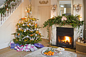 BRUERN COTTAGES, OXFORDSHIRE: CHRISTMAS - THE SITTING ROOM with FIREPLACE, CHRISTMAS TREE AND Ottoman with Bowl of SATSUMAS