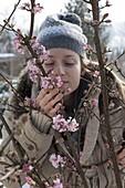 Frau genießt den Duft von Viburnum bodnantense 'Dawn'