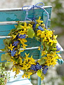 Blau-gelber Frühlingskranz an Stuhllehne