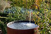 Noun : Altes Wasserfaß mit Kupferhahn im Gemüsegarten
