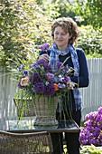 Frau steckt Strauß aus Allium 'Globemaster' (Zierlauch), Rosa (Rosen)