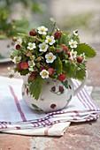 Kleiner Wald-Erdbeer-Strauß (Fragaria vesca) in Kännchen mit Erdbeer-Dekor
