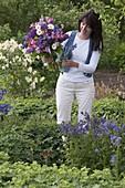 Frau im Garten mit Strauß aus Aquilegia (Akelei), Syringa (Flieder)
