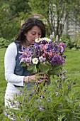 Frau im Garten schnuppert an Strauß aus Aquilegia (Akelei), Syringa (Flieder