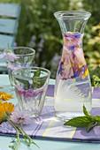 Stilles Wasser mit Minze (Mentha) und Blüten als Getränk