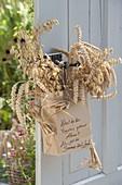 Papiertüte mit Weizen (Triticum) und Hafer (Avena) an Tür gehängt