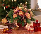 Weihnachtsgesteck aus Zweigen, Rosenblüten und Kugeln