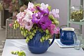 Strauss aus Gladiolus (Gladiolen) und Humulus (Hopfen) in blauem Krug