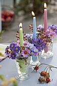 Kerzenglaeser mit Aster (Herbstastern) und Rosa (Hagebutten) in Reihe