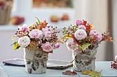 Kleine Herbststraeusse in Vasen verkleidet mit handgeschoepftem Papier