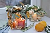 Einmachgläser als Windlichter am Fenster, dekoriert mit Zweigen von Olea