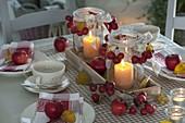 Tischdeko mit Zieräpfeln und Äpfeln