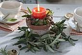 Kerze im Tontopf dekoriert mit Kranz aus Zweigen von Olea (Olive)
