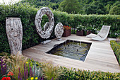 Modernes Wasserbecken mit Holzpodest und Liege, daneben runde Skulpturen aus Treibholz