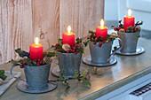 Ungewöhnlicher Adventskranz aus einzelnen Zinkbechern, rote Kerzen, Ilex