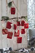 Selbstgemachter Adventskalender mit nummerierten roten Papiertueten