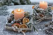 Kleine Holzkästchen mit Kerzen, getrockneten Orangenscheiben (Citrus)