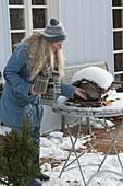 Frau füllt Vogelfutter in Vogelhäuschen auf verschneitem Tisch