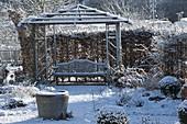 Verschneiter Rosengarten , Holz-Pavillon mit Bank, eingefaßt mit Hecke