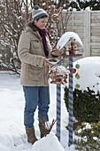 Frau füllt Futter in Vogel-Futterhäuschen auf geringelten Holzpfaehlen
