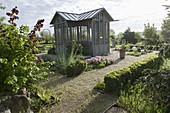 Gartenhaus mit Stauden- und Kraeuterbeeten, Kieswege , Hecke aus Buxus