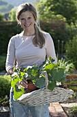 Junge Frau mit Jungpflanzen von Feuerbohnen, Kletterbohnen (Phaseolus)